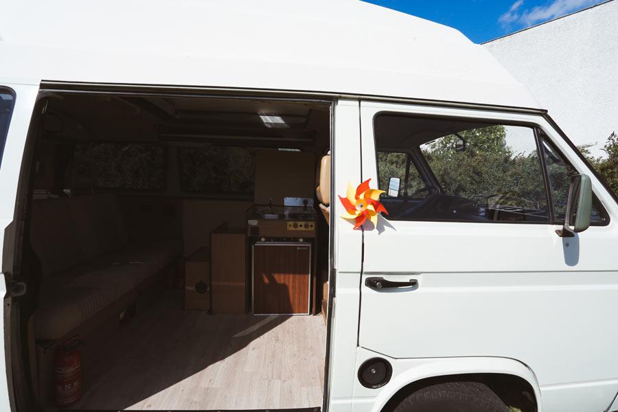 BulliHoliday Camper mieten Carmen - geöffnete Schiebetür zum Wohnraum Bild 2