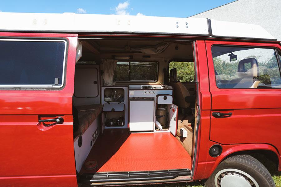 BulliHoliday Campingbus mieten Janine - offene Schiebetür mit Blick in den Wohnraum