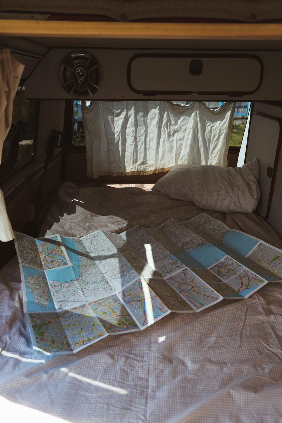 BulliHoliday Campingbus mieten Janine - unteres Bett mit ausgebreiteter Landkarte