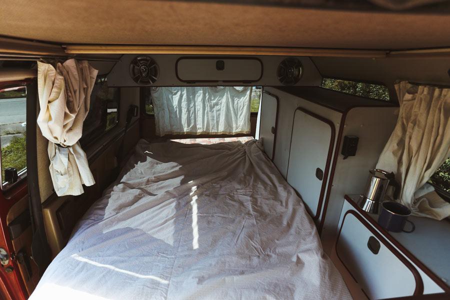 BulliHoliday Campingbus mieten Janine - unteres Bett mit geschlossenen Vorhängen