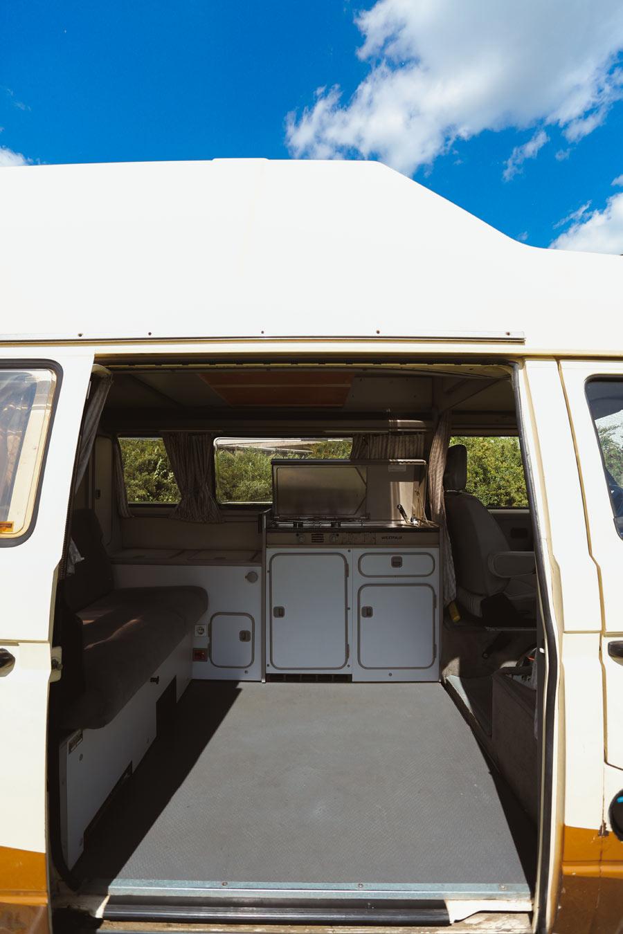 BulliHoliday VW Bulli mieten Kuno - geöffnete Schiebetür und Blick in den Wohnraum mit Schwenk nach links